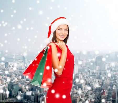 sale, gifts, christmas, holidays and people concept - smiling woman in red dress with shopping bags over snowy city background photo