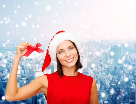 christmas, holidays, winter, happiness and people concept - smiling woman in santa helper hat with jingle bells over snowy city background photo