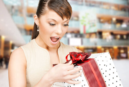 christmas, holidays, valentines day, celebration and people concept - smiling woman in red dress with gift box over shopping center background photo
