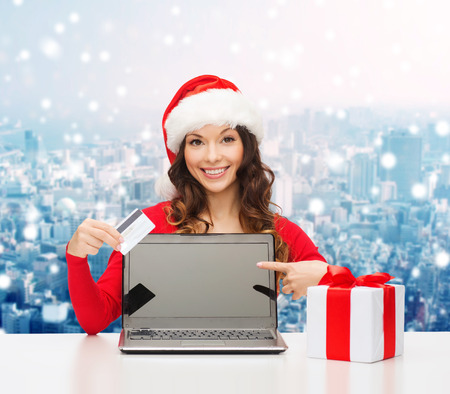 christmas, holidays, technology and people concept - smiling woman in santa helper hat with gift box and laptop computer over snowy city background photo