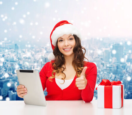 christmas, holidays, technology, gesture and people concept - smiling woman in santa helper hat with gift box and tablet pc computer showing thumbs up over snowy city background photo