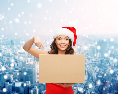 christmas, winter, holidays, delivery and people concept - smiling woman in santa helper hat with parcel box over snowy city background photo