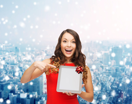 christmas, technology, present and people concept - smiling woman in red dress with blank tablet pc computer screen over snowy city background photo