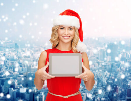 christmas, technology, present and people concept - smiling woman in santa helper hat with tablet pc computer showing blank screen over snowy city background photo