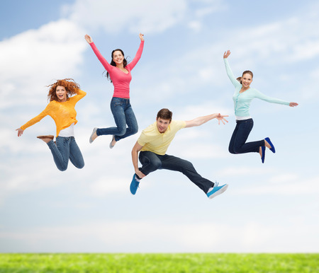happiness, freedom, friendship, movement, summer and people concept - group of smiling teenagers in air over natural background photo
