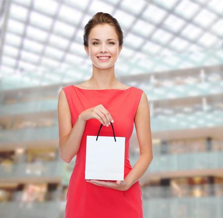 ショッピング、販売、クリスマスとホリデー コンセプト - スモール ショッピング バッグと赤いドレスでエレガントな女性を笑顔