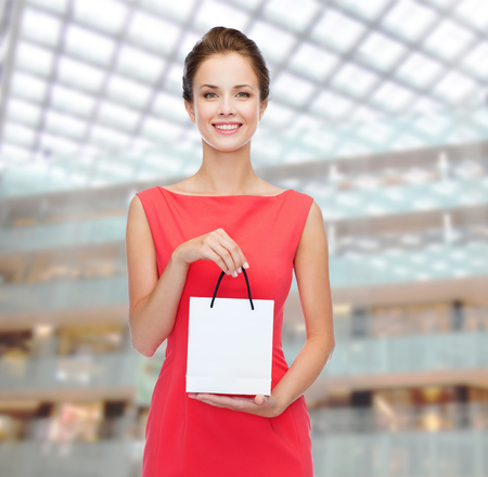 shopping, sale, christmas and holiday concept - smiling elegant woman in red dress with small shopping bag photo