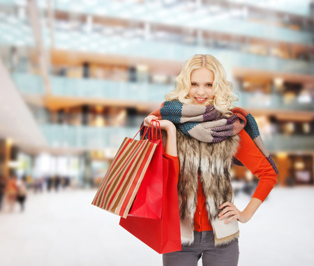 happiness, winter holidays, christmas and people concept - smiling young woman in winter clothes with red bags over shopping center background photo