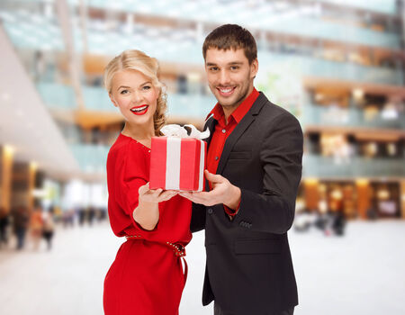 christmas, holidays, valentines day, celebration and people concept - smiling man and woman with present over shopping centre background photo