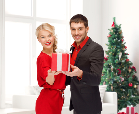 christmas, holidays, valentines day, celebration and people concept - smiling man and woman with present over living room and christmas tree background photo