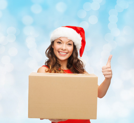 approvement: christmas, winter holidays, delivery, gesture and people concept - smiling woman in santa helper hat with parcel box showing thumbs up over blue lights background