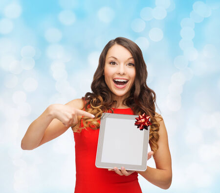 christmas, technology, present and people concept - smiling woman in red dress with blank tablet pc computer screen over blue lights background photo