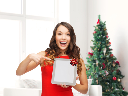 christmas, technology, present and people concept - smiling woman in red dress with blank tablet pc computer screen over living room and christmas tree background photo