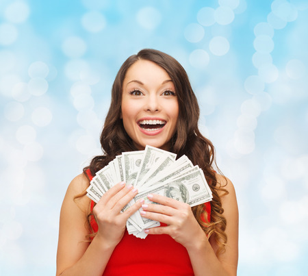 christmas, sale, banking, winning and holidays concept - smiling woman in red dress with us dollar money over blue lights background Stock Photo