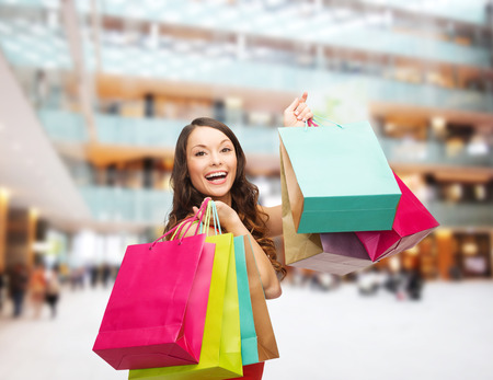 sale, gifts, holidays and people concept - smiling woman with colorful bags over shopping center background photo