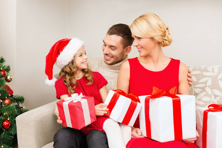 family, christmas, x-mas, winter, happiness and people concept - smiling family in santa helper hats with many gift boxes photo