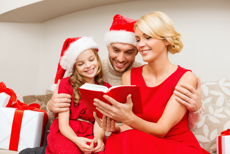 family, christmas, x-mas, winter, happiness and people concept - smiling family in santa helper hats with many gift boxes reading book photo