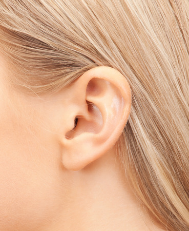 human ear: hearing, health, beauty and piercing concept - close up of womans ear