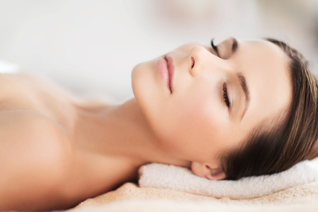 dayspa: beauty and spa concept - beautiful woman in spa salon lying on the massage desk