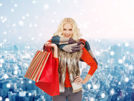happiness, winter holidays, christmas and people concept - smiling young woman in winter clothes with red shopping bags over snowy city background photo