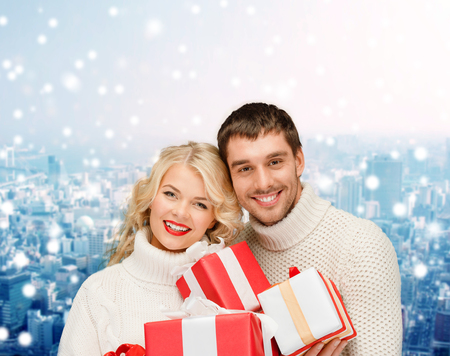 christmas, holidays, happiness and people concept - smiling man and woman with presents over snowy city background photo