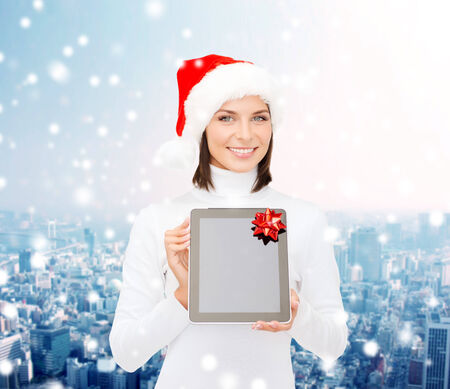 christmas, technology, present and people concept - smiling woman in santa helper hat with blank screen tablet pc computer over snowy city background photo