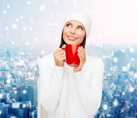 happiness, winter holidays, christmas, beverages and people concept - smiling young woman in white warm clothes with red cup over snowy city background photo