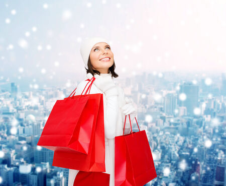 happiness, winter holidays, christmas and people concept - smiling young woman in white hat and mittens with red shopping bags over snowy city background photo