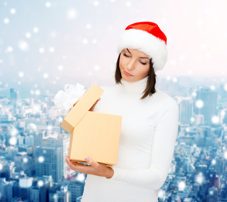 santa helper: christmas, winter, happiness, holidays and people concept - woman in santa helper hat with gift box over snowy city background