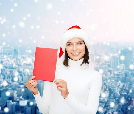 christmas, holidays, celebration, greeting and people concept - smiling woman in santa helper hat with greeting card over snowy city background photo