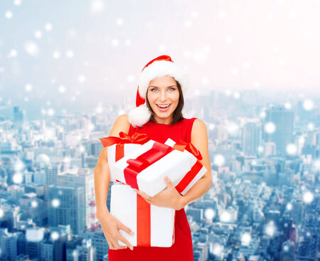 christmas, winter, happiness, holidays and people concept- smiling woman in santa helper hat with gift boxes over snowy city background photo