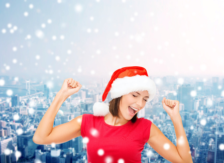christmas, winter, holidays, happiness and people concept - smiling woman in santa helper hat and blank red shirt over blue city background photo