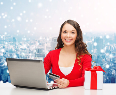 christmas, holidays, technology and shopping concept - smiling woman with credit card, gift box and laptop computer over snowy city background photo