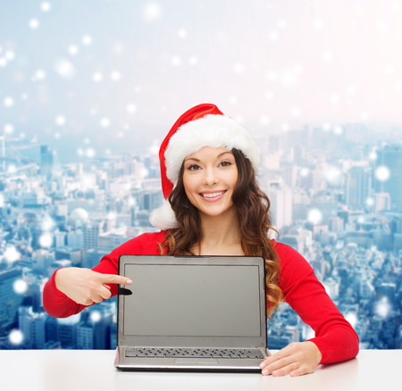 christmas, holidays, technology, advertisement and people concept - smiling woman in santa helper hat pointig finger to blank laptop computer screen over snowy city background photo