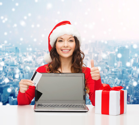 christmas, holidays, technology and shopping concept - smiling woman in santa helper hat with credit card, gift box and laptop computer showing thumbs up gesture over snowy city background photo