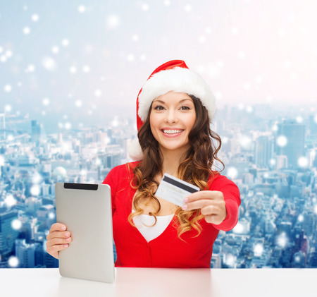 christmas, technology, shopping and people concept - smiling woman in santa helper hat with tablet pc computer and credit card over snowy city background photo
