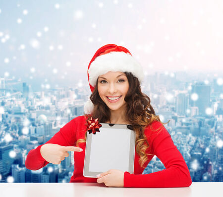 christmas, holidays, technology and people concept - smiling woman in santa helper hat with tablet pc computer over snowy city background photo