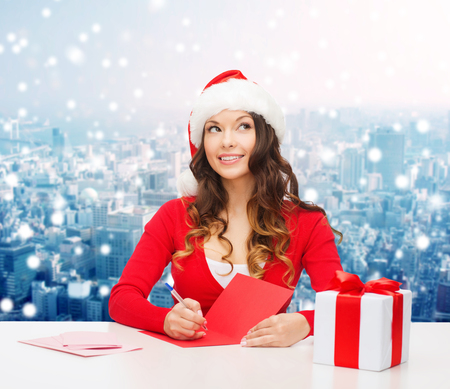 santa helper: christmas, holidays, celebration, greeting and people concept - smiling woman in santa helper hat with gift box writing letter or sending post card over snowy city background