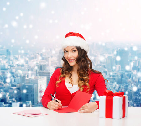 christmas, holidays, celebration, greeting and people concept - smiling woman in santa helper hat with gift box writing letter or sending post card over snowy city background photo