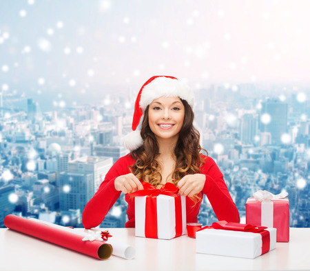 christmas, holidays, celebration, decoration and people concept - smiling woman in santa helper hat with decorating paper packing gift boxes over snowy city background photo