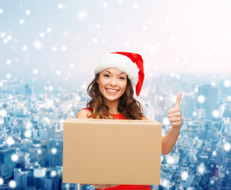 approvement: christmas, winter holidays, delivery, gesture and people concept - smiling woman in santa helper hat with parcel box showing thumbs up over snowy city background Stock Photo