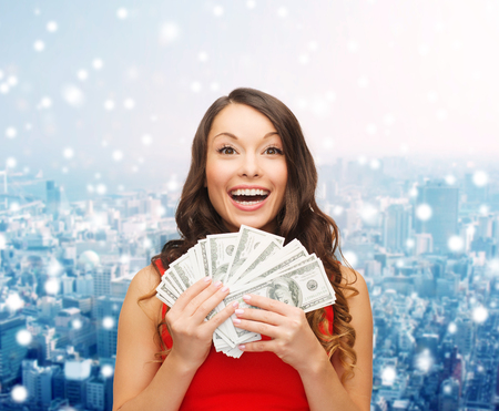 win money: christmas, sale, banking, winning and holidays concept - smiling woman in red dress with us dollar money over snowy city background
