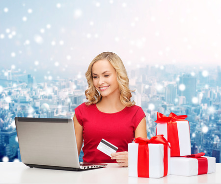 christmas, holidays, technology and shopping concept - smiling woman in red blank shirt with gift boxes, credit card and laptop computer over blue lights background photo