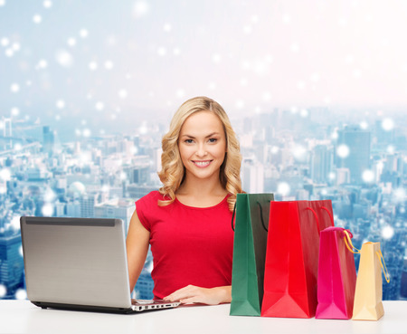 christmas, holidays, technology, advertising and people concept - smiling woman in red blank shirt with shopping bags and laptop computer over snowy city background photo