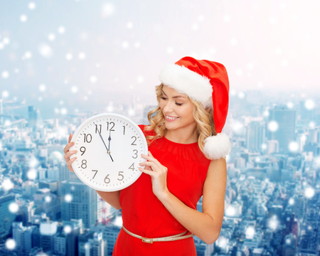 christmas, winter, holidays, time and people concept - smiling woman in santa helper hat and red dress with clock over snowy city background photo
