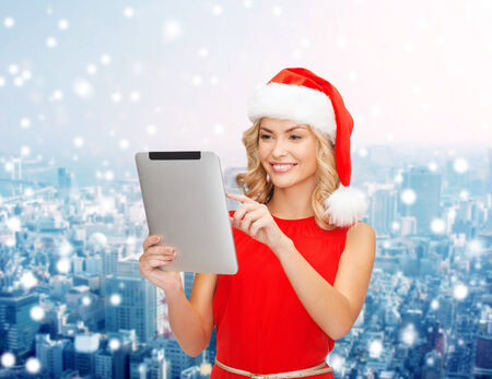 christmas, technology, present and people concept - smiling woman in santa helper hat with tablet pc computer over snowy city background photo