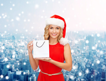 sale, gifts, christmas, holidays and people concept - smiling woman in red dress and santa helper hat with white blank shopping bag over snowy city background photo