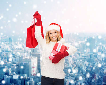 happiness, winter holidays, christmas and people concept - smiling young woman in santa helper hat with gifts and shopping bag over snowy city background photo