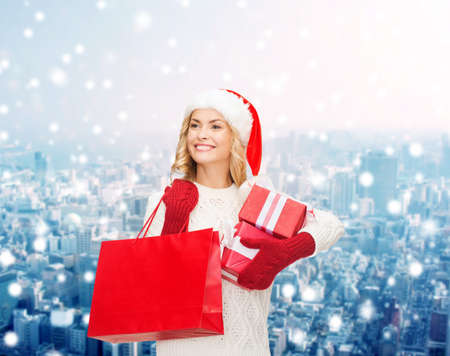 happiness, winter holidays, christmas and people concept - smiling young woman in santa helper hat with gift boxes and shopping bag over snowy city background photo