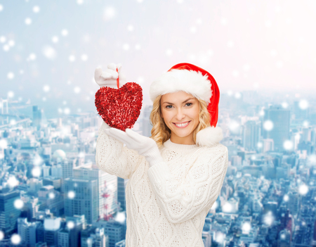 happiness, winter holidays, christmas and people concept - smiling young woman in santa helper hat with red heart decoration over snowy city background photo